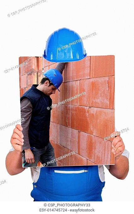 Builder hiding behind picture of construction site