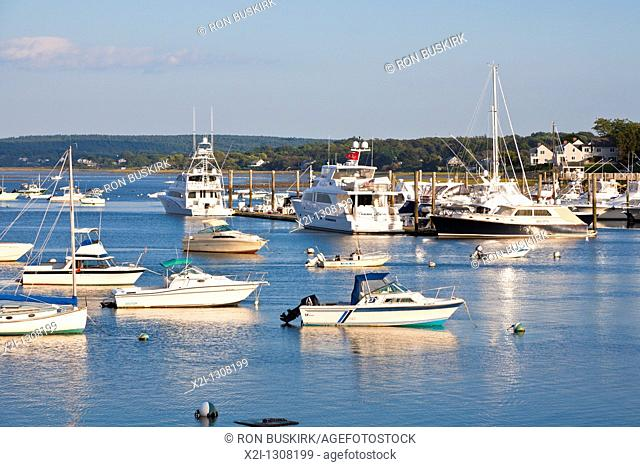 Boats moored at low tide in Plymouth Harbor at dawn in Plymouth Massachusetts