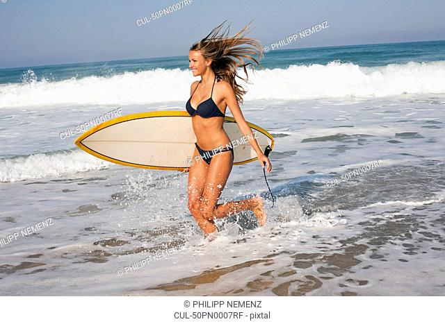 Woman carrying surfboard in waves