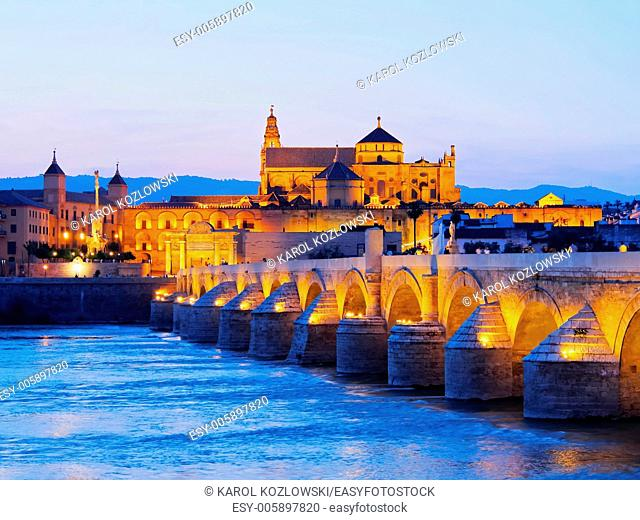 Night view of Mezquita-Catedral and Puente Romano - Mosque-Cathedral and the Roman Bridge in Cordoba, Andalusia, Spain