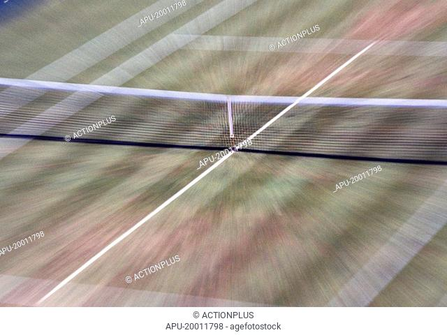 Blurred view of grass tennis court and net