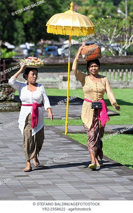 Women in traditional dress carrying a basket with offerings on their heads, going to a ceremony in the royal temple of Pura Taman Ayun, Mengwi, Bali, Indonesia