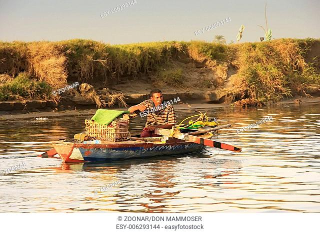 Local man paddling boat on the Nile river, Luxor