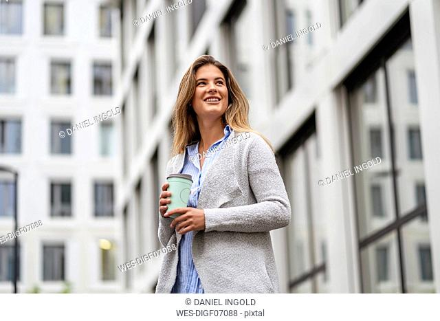 Young businesswoman with coffee to go cup, office building in the background