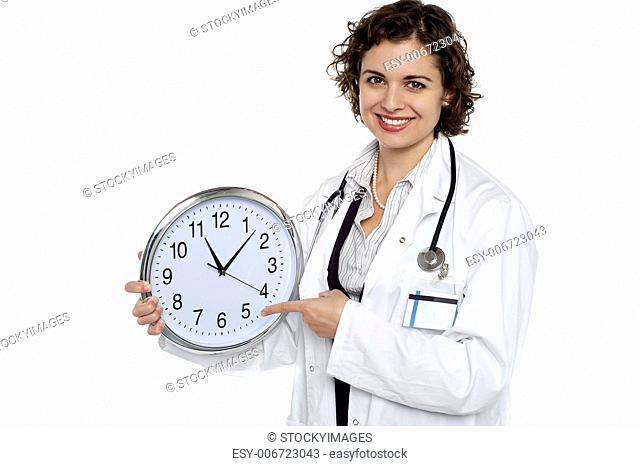 Attractive medical practitioner with a clock in hand pointing out the time