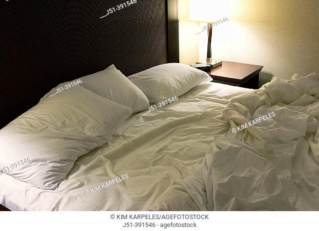 TEXAS San Antonio. Unmade kingsize bed, lamp on end table, pillows and sheets mussed