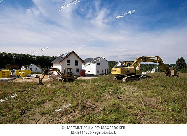 Developement area, view of the area, two excavators at front, first finished homes at back, North Rhine-Westphalia, Germany, Europe, PublicGround