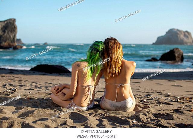USA, California, West Coast, back view of two young women sitting head to head on the beach