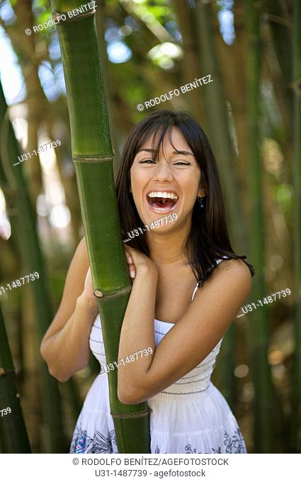 Latin woman in bamboo forest smiling at camera