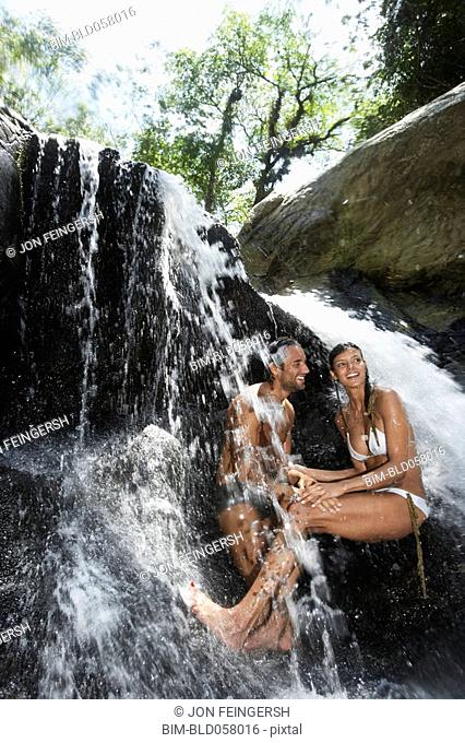 Hispanic couple sitting under waterfall