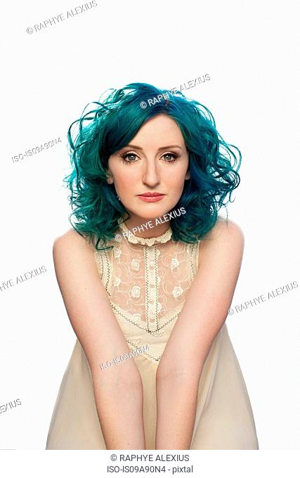 Young woman with green hair in front of white background, portrait