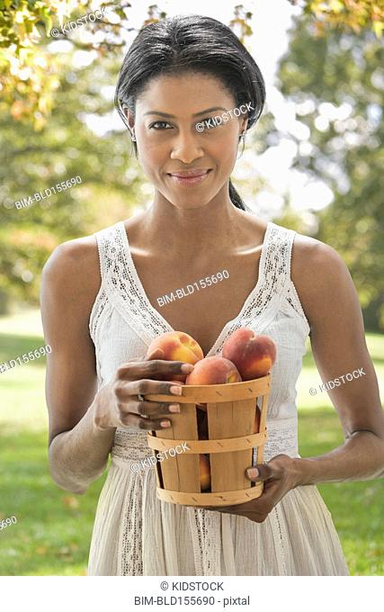 Hispanic woman picking apples in orchard