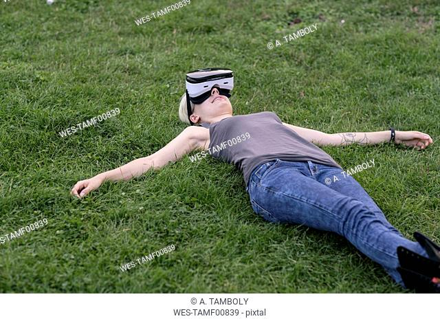 Young woman lying on a meadow wearing Virtual Reality Glasses outdoors