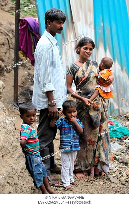 A poor Indian family of father mother and three children standing at the construction site they work at