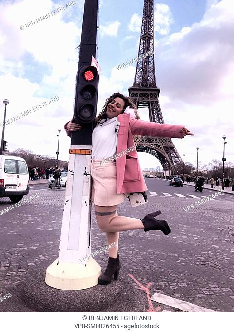 young happy Millennial tourist woman dancing at street embracing red traffic lights, next to touristic sight Eiffel Tower, in Paris, France