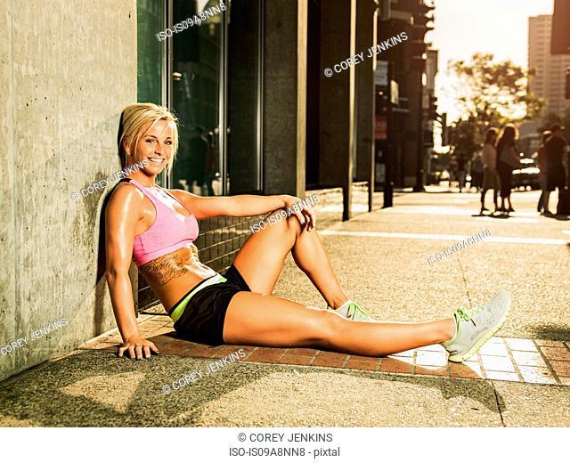 Female runner sitting on sidewalk