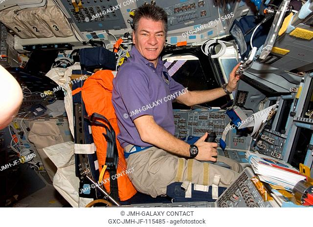 European Space Agency astronaut Paolo Nespoli, Expedition 26 flight engineer, occupies the commander's station on the flight deck of space shuttle Discovery...