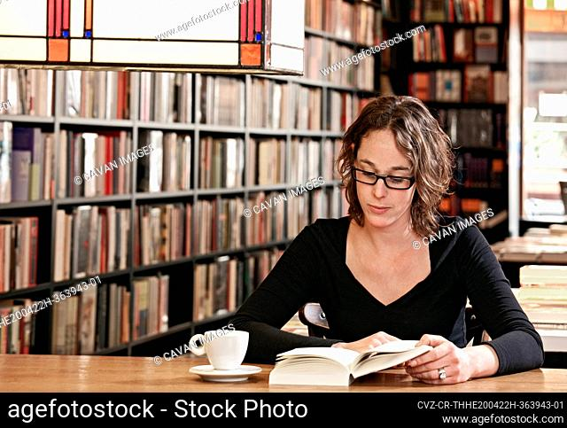 woman drinking coffee while reading at bookstore