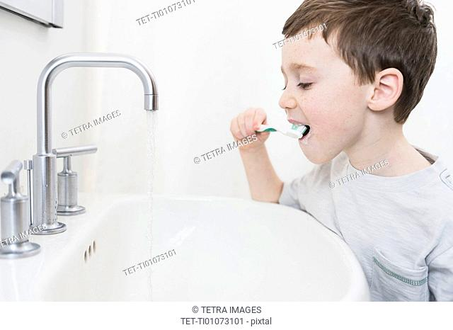 boy (6-7) brushing teeth