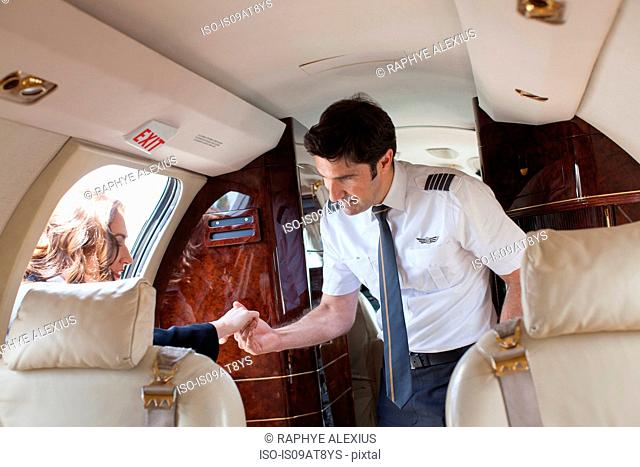 Male pilot helping female client board private jet