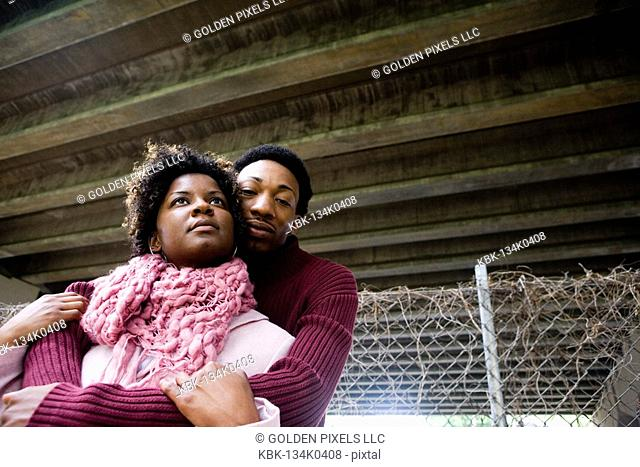 Young couple standing under a highway overpass