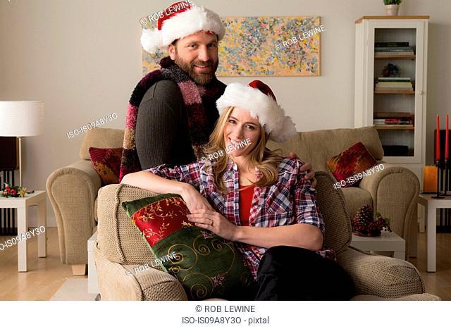 Husband and wife in Santa hat looking at camera