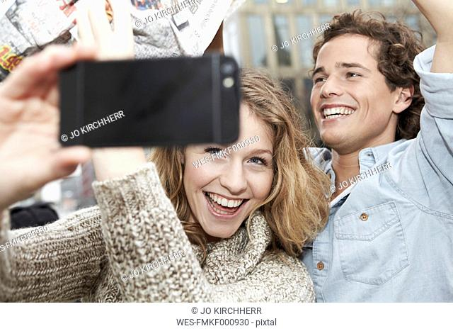 Portrait of happy young couple photographing themself with smart phone, studio shot