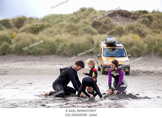 Family with two boys playing on beach