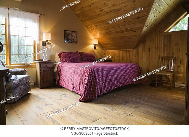King size bed and antique wooden sitting chair in master bedroom on the upstairs floor inside a cottage style log home, Quebec, Canada