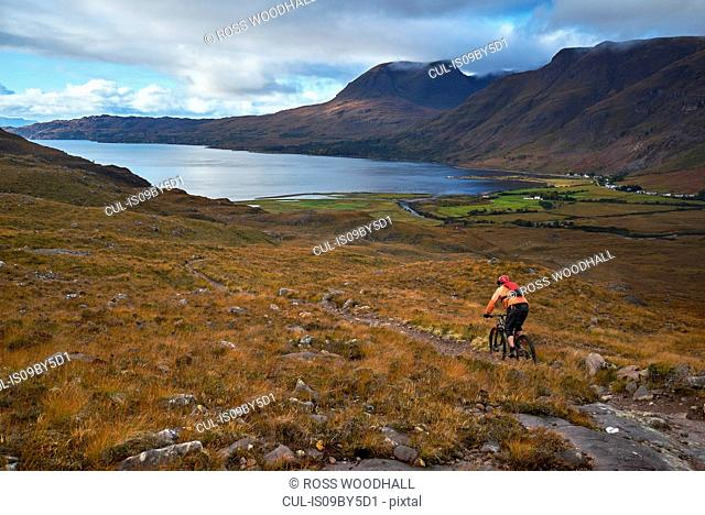 Male mountain biker biking down dirt track in mountain valley landscape, elevated view, Achnasheen, Scottish Highlands, Scotland