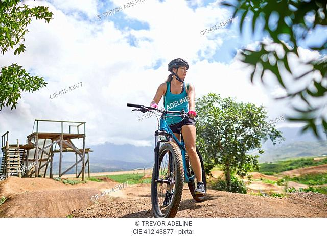 Woman mountain biking at sunny obstacle course