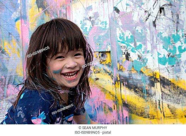 Portrait of girl by painted wall looking at camera smiling