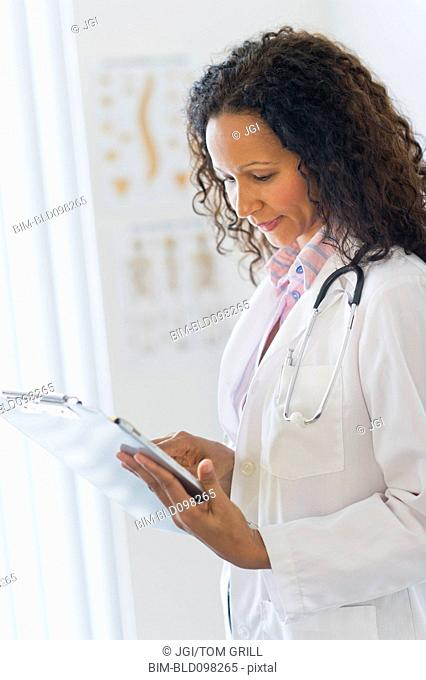Hispanic doctor looking at medical chart in hospital