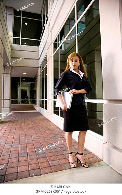 Portrait of Hispanic businesswoman holding laptop outside office building