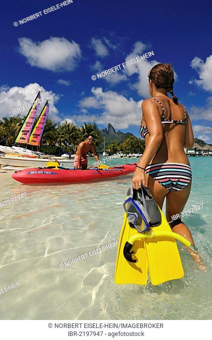 Woman taking snorkelling equipment to a kayak, St. Regis Bora Bora Resort, Bora Bora, Leeward Islands, Society Islands, French Polynesia, Pacific Ocean