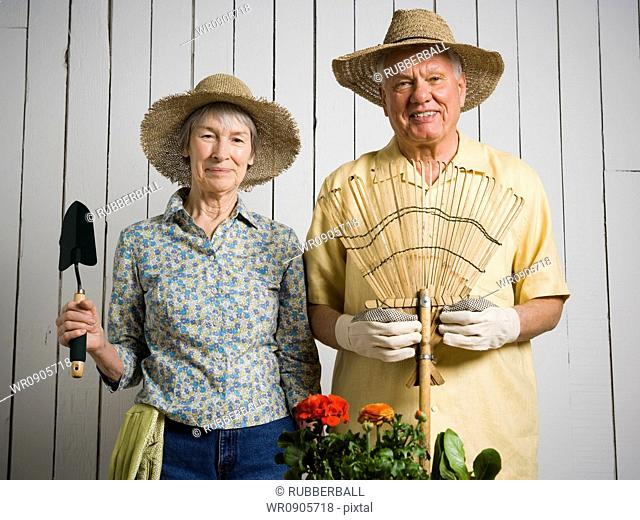 Portrait of an elderly couple standing with gardening tools