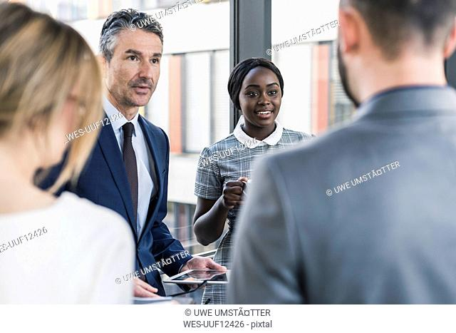 Business people with tablet talking on office floor