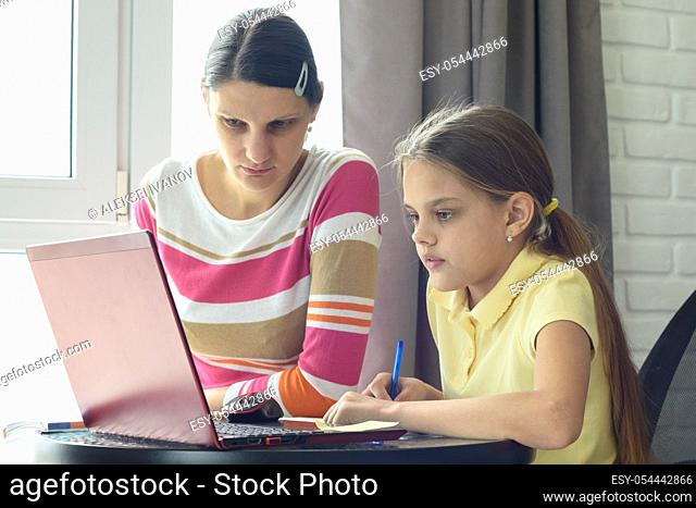 Mom and daughter solve homework using online distance learning