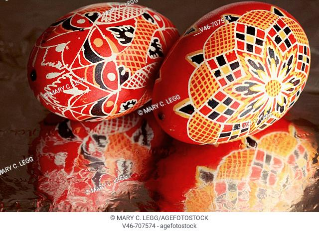 Two large  red handpainted Czech Easter Eggs with abstract geometrical designs on a highly reflective surface. Two goose eggs painted wtih red background with...
