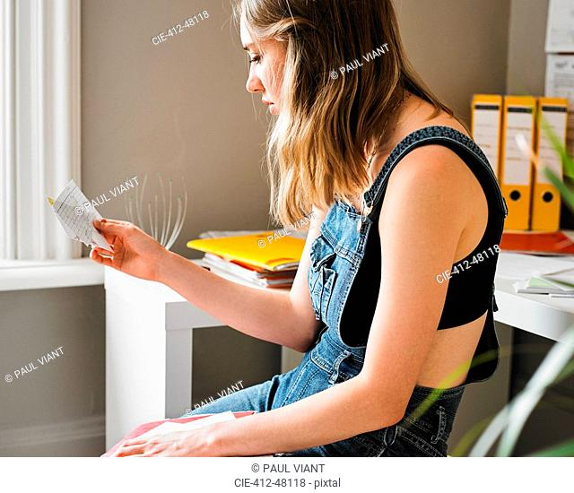 Young female college student studying with flash cards