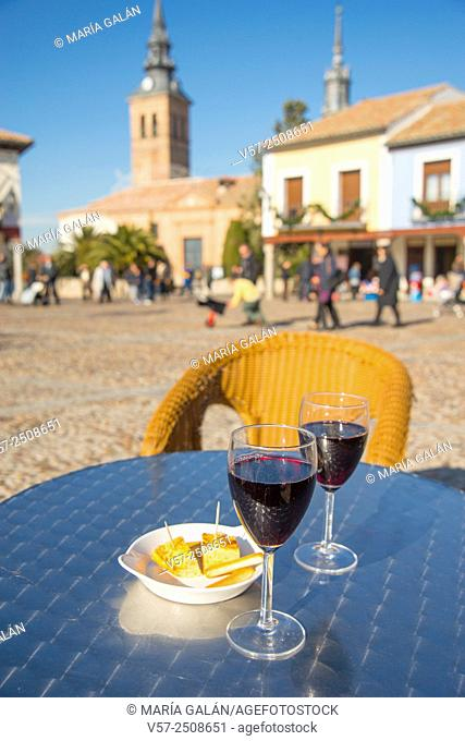 Two glasses of red wine with tapa of Spanish omelet in a terrace. Segovia Square, Navalcarnero, Madrid province, Spain