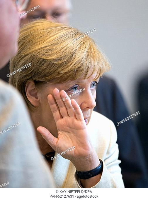 German Chancellor Angela Merkel (CDU) talks to a member of the parliament while covering the side of her face with her hand