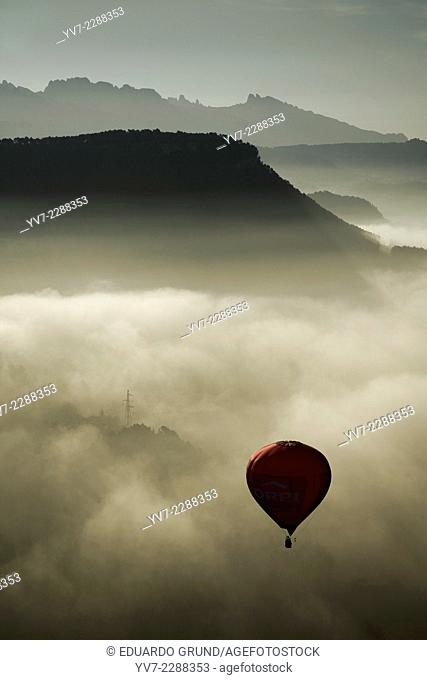Red balloon flying over a cloud layer in European hot air balloon festival Igualada, Barcelona, Catalonia, Spain, Europe
