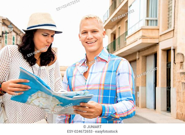 Trendy attractive young couple of tourists consulting a map as they search for their destination while out sightseeing on their summer vacation