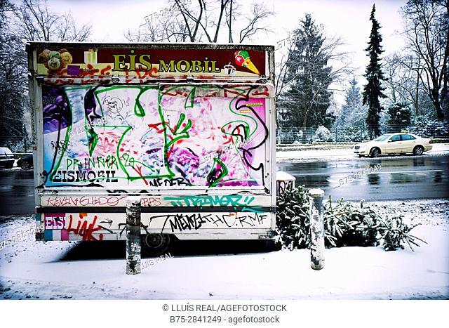 Carro mobil cerrado y aparcado en una calle pintado con graffiti una mañana de invierno nevado. Neukölln, Berlin, Alemania, Europa
