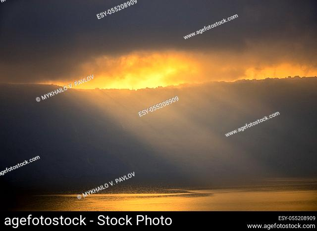 Heavy clouds over the rocky shore. The sun's rays barely break through, illuminate small houses and the water surface