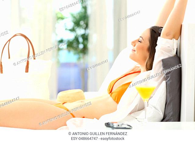 Happy woman relaxing lying on a bed of an hotel room on summer vacations