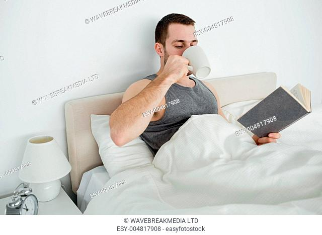 Smiling man reading a novel while drinking a coffee