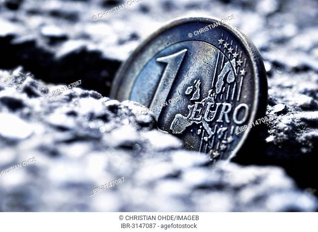 A one euro coin sticking in crevice, symbolic image for euro crisis