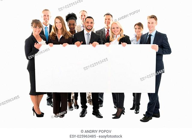 Portrait of confident multi ethnic business team holding blank billboard against white background